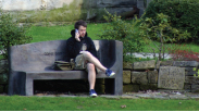 Photo of student on a park bench.