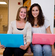 Two girls holding laptop computers. Link to Most Popular Options.